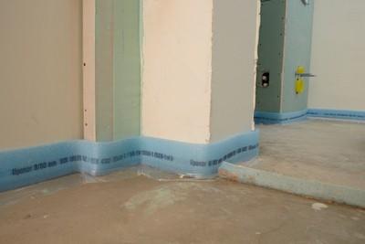 Чтобы стяжка не деформировалась, стены желательно проклеить демпферной лентой