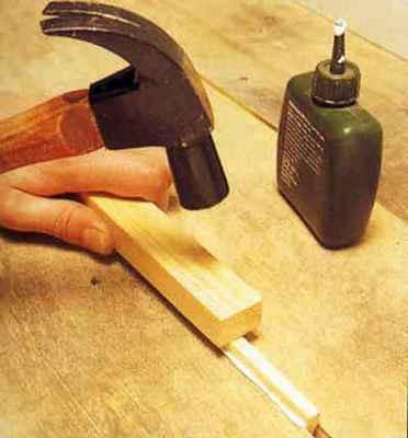 Забивание рейки в щель обычным молотком через деревянную прокладку