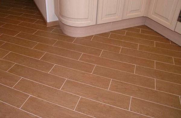 Плитка под дерево уложена по диагонали со смещением на кухне и в коридоре без перехода