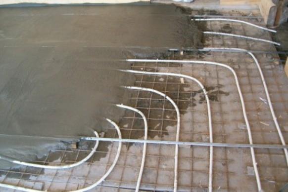 Укладка цементной стяжки поверх труб теплого пола