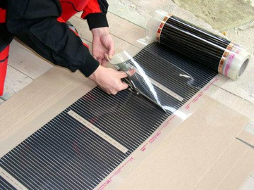 Уложить сверху плёночный тёплый пол, отрезая в обозначенных символом ножниц местах куски нужной длины от рулона