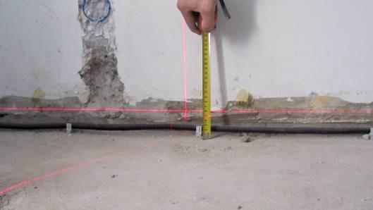 С помощью уровнемера на стенах выполняют разметку нулевого уровня,