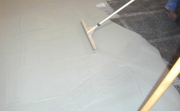 Готовый раствор выливают из ведра на основание и с помощью ракли разгоняют его вдоль стены