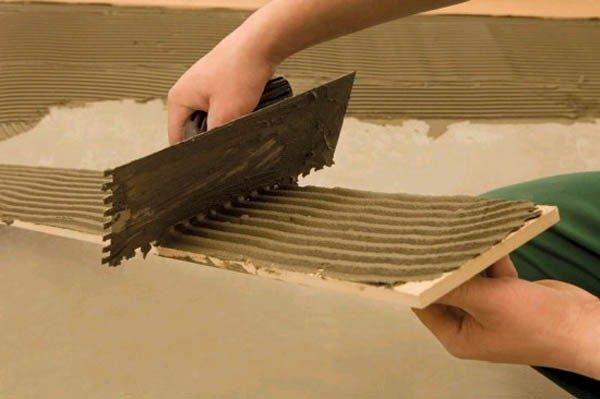 Клей наносят и на плитку, и на пол для лучшего сцепления и предотвращения появления пустот