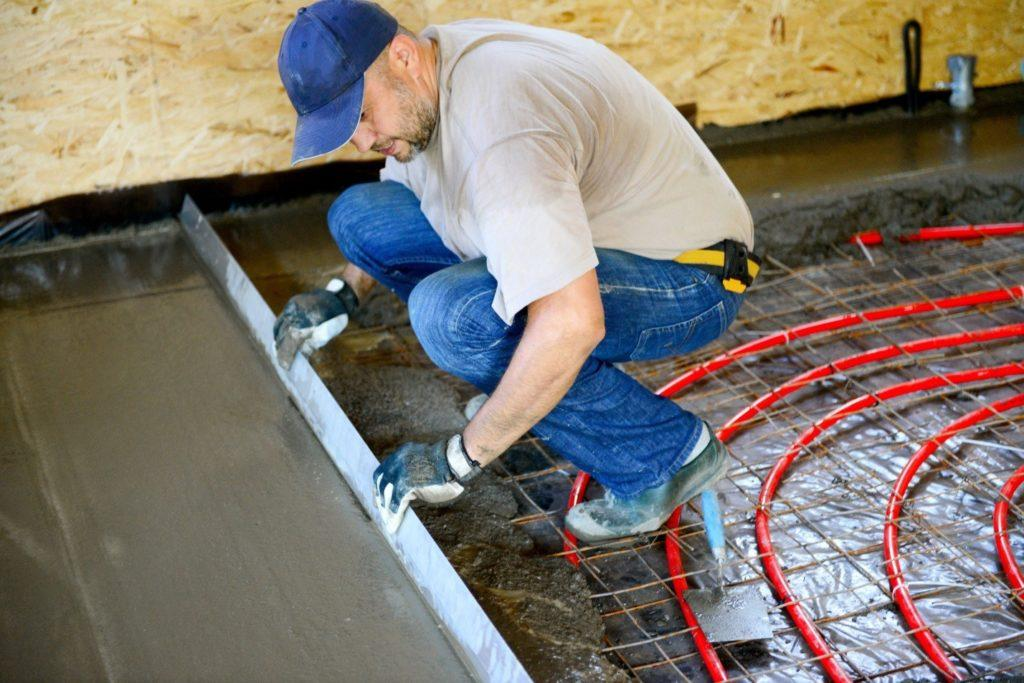 Поверх теплого пола делается еще один слой стяжки – обратите внимание, что под сеткой настелена гидроизоляционная пленка