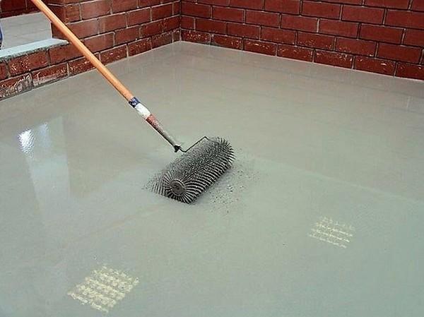 Распределение раствора самовыравнивающей стяжки по бетону осуществляется с помощью игольчатого валика и широкого шпателя