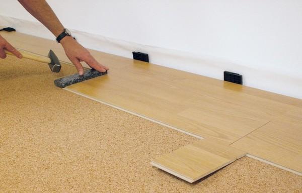 Стоит постепенно укладывать материалы: сначала один участок пробки, сверху ламинат, затем – рядом снова пробка и ламинат