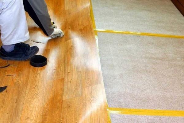 Чтобы правильно обрезать линолеум с учетом всех особенностей помещения, его нужно временно прикрепить к фанере с помощью двухстороннего скотча