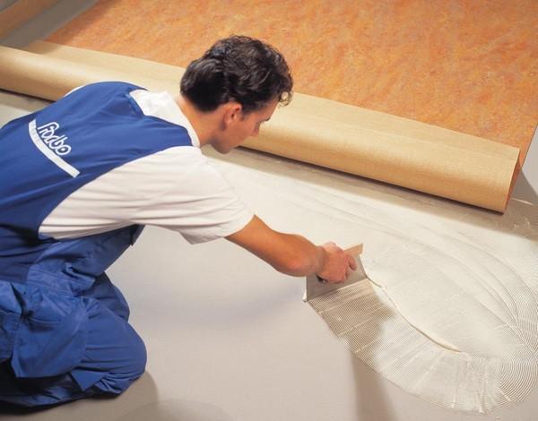 Использование клея для фиксации линолеума к деревянному полу позволяет избежать таких неприятностей, как появление волн, вздутия и проч.